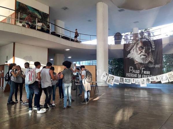 No hall do prédio da Reitoria, estudantes conversam em grupo. Ao fundo, bandeira pendurada no mezanino traz a imagem de Paulo Freire com os dizeres: Educação não é mercadoria, Paulo Freire patrono da Educação